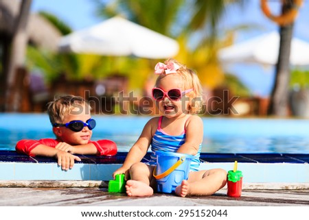 little boy and girl playing in swimming pool at the beach - stock photo
