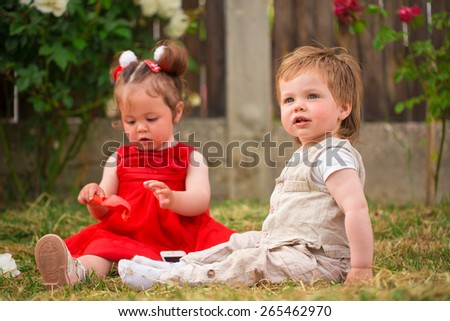 Little boy and girl playing in the garden - stock photo