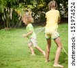 Little boy and girl playing on the lawn. - stock photo
