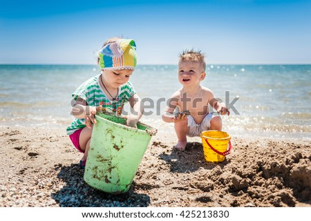 little boy and girl playing on the seashore