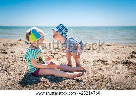 little boy and girl playing on the seashore - stock photo