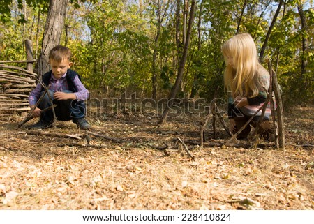 Little boy and girl playing together outdoors in woodland building wooden tepees from small twigs and branches