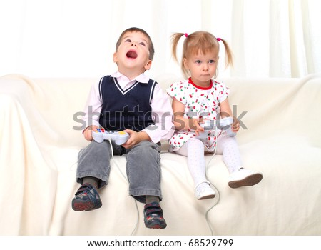 Little boy and girl playing tv game on sofa - stock photo