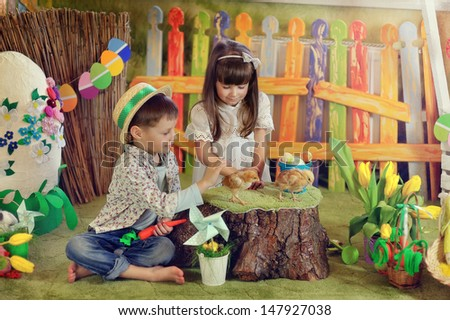 little boy and girl playing with a chicken on a fabulous farm - stock photo