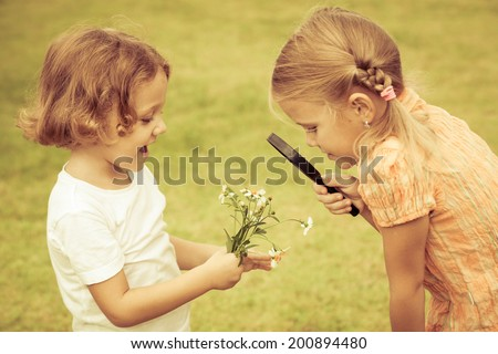 little boy and girl playing with a magnifying glass at day time - stock photo