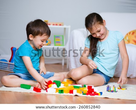 Little boy and girl playing with toys - stock photo