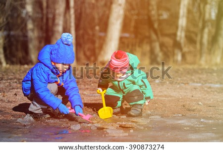 little boy and girl playing with water in spring - stock photo