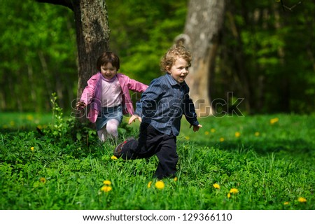 little boy and girl running away in the park - stock photo
