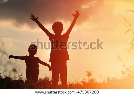 little boy and girl silhouettes play at sunset