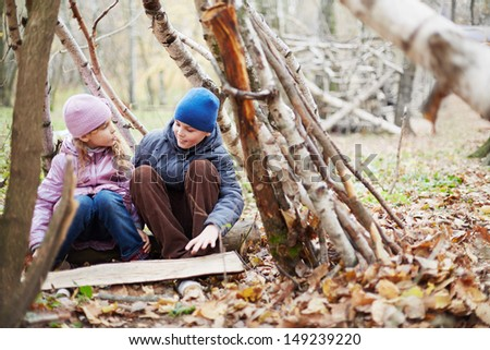 Little boy and girl sit in hut built between birches in autumn park and talk - stock photo