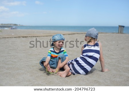 Little boy and girl sitting on the beach