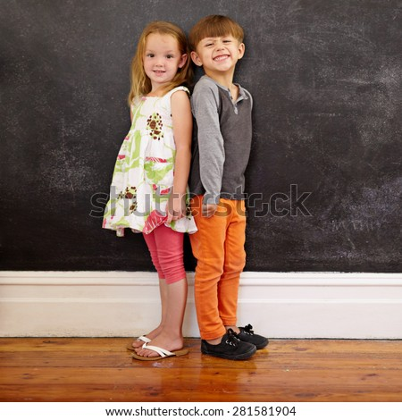 Little boy and girl standing back to back in front of blackboard looking at camera smiling. Full length image of two innocent little children together at home. - stock photo