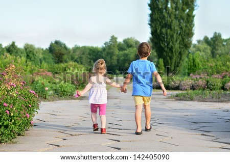 Little boy and girl walking hand in hand in the park - stock photo
