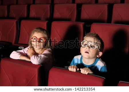 Little boy and girl watching a movie with interest in an empty cinema hall - stock photo