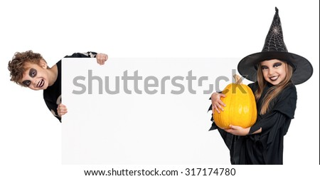 Little boy and girl wearing Halloween costume with pumpkin and blank board on white background - stock photo