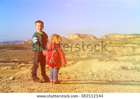 little boy and girl with backpacks travel in mountains - stock photo