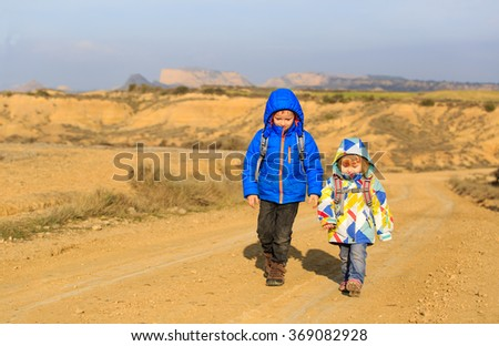 little boy and girl with backpacks travel on the road - stock photo