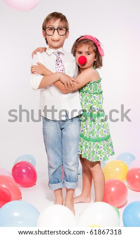 Little boy and girl with fake noses in a balloon party - stock photo