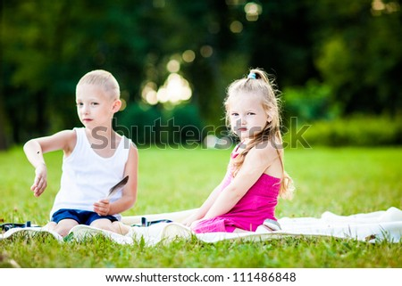Little boy and girl  with ladybird in park during beautiful summer evening