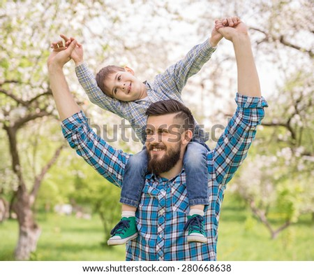 Little boy and his dad enjoying their time together outside in nature. - stock photo