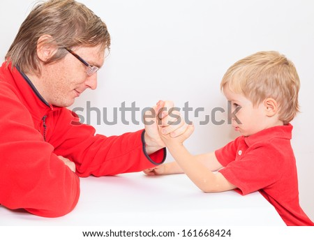 Little boy and his father arm wrestling - stock photo