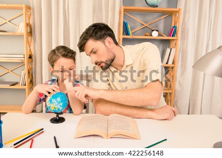 Little boy and his father learning geography at home - stock photo