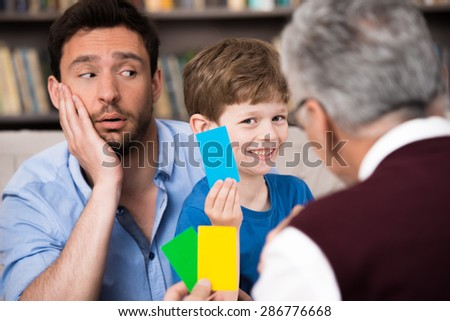 Little boy and his father talking with psychologist. Psychologist making test with boy. Boy making wrong choice. There are many books in psychologist office - stock photo