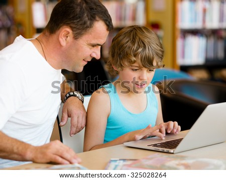 Little boy and his father with laptop in library