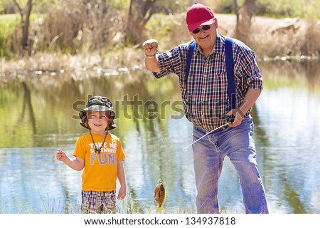 Little Boy and His Grandpa catching a fish - stock photo