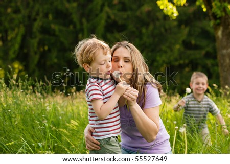 Little boy and his mother blowing dandelion seed for a whish on a meadow outdoors in summer, in the background his brother is running