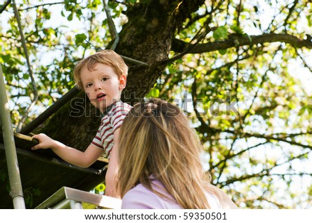 Little boy and his mother climbing up a ladder, they want to reach their tree house (house not to be seen) - stock photo
