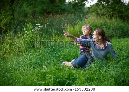 Little boy and his mother enjoying sunset and sitting on grass in summer forest near lake