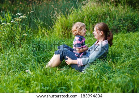 Little boy and his mother having fun together in nature landscape