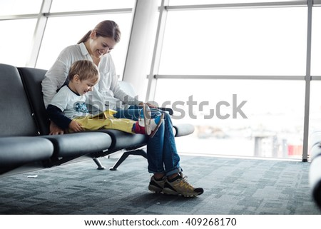Little boy and his mother sitting in an airport departure hall and playing on a tablet  - stock photo