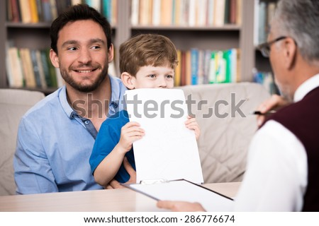 Little boy and his smiling father talking with psychologist. Boy holding white sheet of paper. Psychologist taking notes. There are many books in psychologist office - stock photo