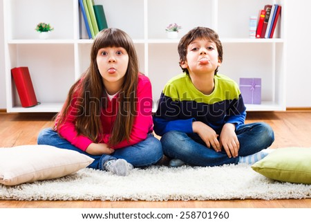 Little boy and little girl are sitting in living room and sticking out their tongue.Children sticking out tongue - stock photo