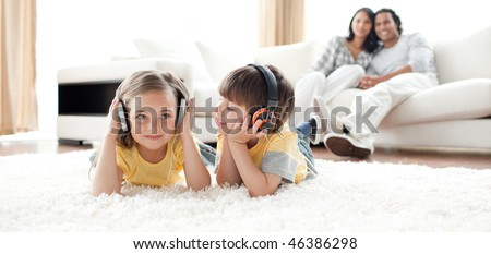 Little boy and little girl playing on the floor with headphones in the living room - stock photo