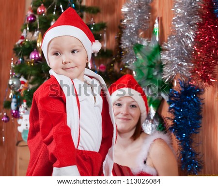 Little boy and mother in Christmas hat at home - stock photo
