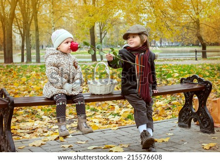 little boy and small girl with a rose on a bench in the autumn Park  - stock photo
