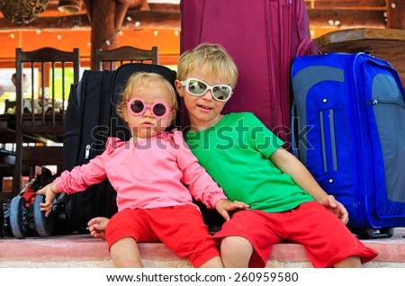 little boy and toddler girl sitting on suitcases ready to travel, kids travel