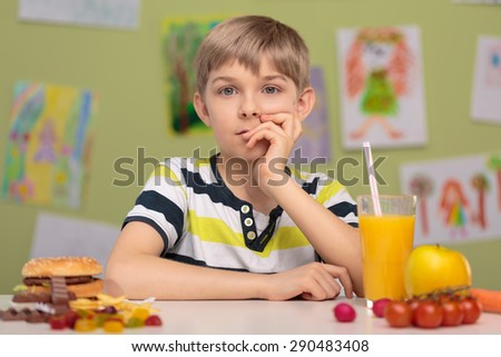 Little boy and tough choice for food for lunch - stock photo