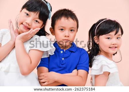 little boy and two little girl standing posing in studio - stock photo