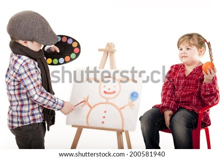 little boy as a visual artist in gym picture hats and a girl with braids and orange in her hand brush and water colors / little boy as an artist painting girl - stock photo