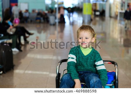 little boy at airport riding on luggage cart
