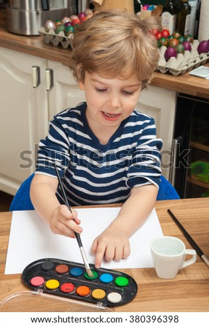 Little boy at home drawing with watercolors. Creative kid painting at home with watercolors.  - stock photo
