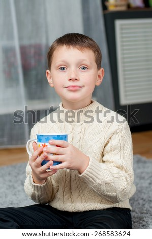 little boy at home on the carpet with a cup of tea