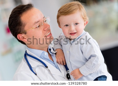 Little boy at the hospital being held by a doctor - stock photo