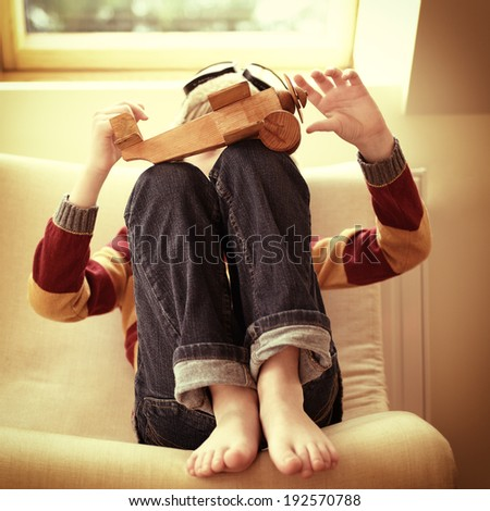 Little boy aviator dreaming and playing with wooden handmade toy plane at home, vintage toned - stock photo