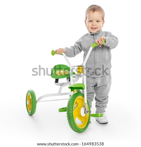Little boy beside tricycle with clipping path - stock photo