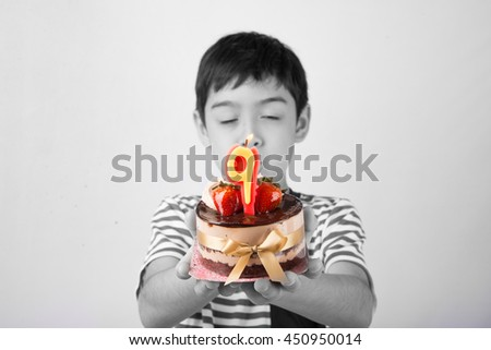 Little boy blowing candle on the cake for his birthday - stock photo